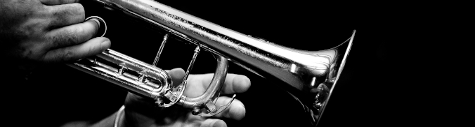 Pictured is a trumpet being played by someone.